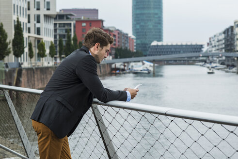Germany, Hesse, Frankfurt, young businessman standing on a bridge using his smartphone - UUF001832