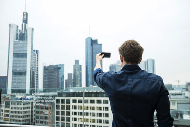 Germany, Hesse, Frankfurt, young man taking a picture of the skyline with his smartphone - UUF001846