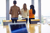 Three creative people standing side by side in a conference room looking out of window - ZEF000909