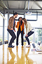 Three happy creative people dancing on a conference table - ZEF000911