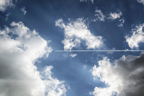 Vapour trails of a plane in sky with clouds - OPF000008