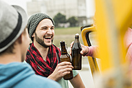 Group of friends drinking beer outdoors - UUF001848