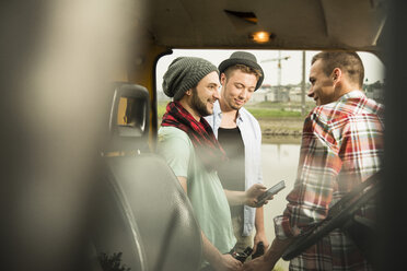 Group of friends with cell phone at a car - UUF001877
