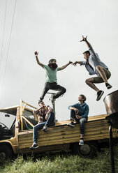 Two friends jumping from pick-up truck - UUF001879