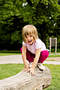 Little girl on playground crouching on log - LVF001890