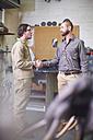 Two men in a sculptor's workshop shaking hands - ZEF000356