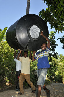 Haiti, Charle Magne, Young man carrying water tank - FLK000456