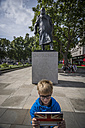 UK, London, boy standing in front memorial for Winston Churchill taking a selfie with his digital tablet - PAF000953