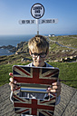 UK, Cornwall, boy taking a selfie in front of direction sign at Land's End with his digital tablet - PAF000963