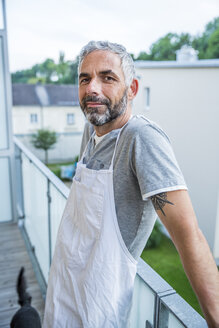 Portrait of smiling man with apron standing on his balcony - MBEF001272