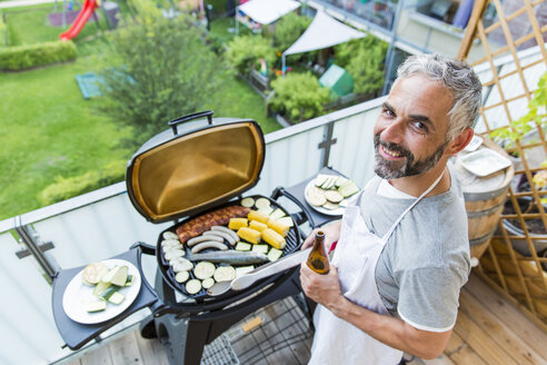 Smiling man barbecuing on his balcony - MBEF001274