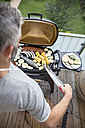 Man barbecuing on his balcony - MBEF001275