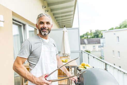 Portrait of smiling man with apron and tongs on his balcony - MBEF001280
