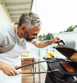 Man barbecuing on his balcony - MBEF001282