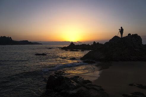 Spain, Catalonia, Lloret de Mar, Platja de Santa Christina, Silhouette of a photographer at sunrise - PU000086