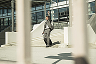 Businessman with suitcase outside office building hailing a taxi - UUF001951