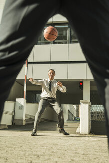 Two businessmen playing basketball outside office building - UUF001961