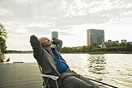 Germany, Frankfurt, relaxed businessman at river Main - UUF001981