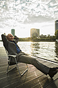 Germany, Frankfurt, relaxed businessman at river Main - UUF001988
