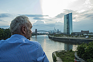 Germany, Frankfurt, businessman at river Main with European Central Bank Headquarters in background - UUF001995