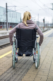 Woman in wheelchair waiting at station platform - EJWF000604