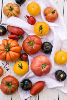 Different heirloom tomatoes on white wood and cloth - SARF000852