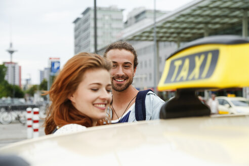 Germany, Berlin, Young couple taking taxi - FKF000666