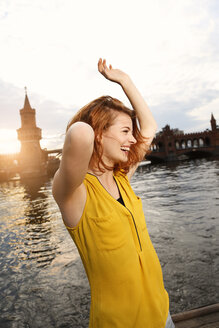 Germany, Berlin, Young woman enjoying sunset at Spree river - FKF000675