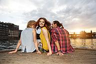 Germany, Berlin, Friend sitting at Spree river, enjoying sunset - FKF000688