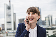 Germany, Hesse, Frankfurt, portrait of smiling businesswoman telephoning in front of skyline - FMKYF000519