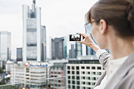 Germany, Hesse, Frankfurt, woman taking a picture of the skyline with her smartphone - FMKYF000523