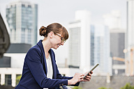 Germany, Hesse, Frankfurt, smiling businesswoman using her digital tablet - FMKYF000538