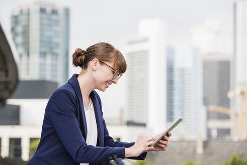 Germany, Hesse, Frankfurt, smiling businesswoman using her digital tablet - FMKYF000538