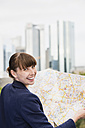 Germany, Hesse, Frankfurt, portrait of smiling woman with city map - FMKYF000542