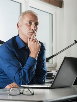 Mature businessman at desk thinking - UUF001923