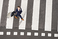 Germany, businesswoman with rolling suitcase walking on zebra crossing, view from above - FMKYF000551
