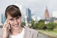 Germany, Hesse, Frankfurt, portrait of smiling businesswoman telephoning with smartphone - FMKYF000554
