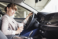 Germany, Hesse, Frankfurt, portrait of smiling businesswoman driving car with coffee to go in one hand - FMKYF000575