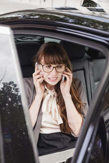 Germany, businesswoman sitting in a car using two smartphones - FMKYF000583