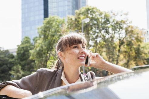Portrait of smiling businesswoman telephoning with smartphone - FMKYF000601