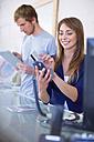 Shop assistant putting credit card in credit card reader - ZEF000486