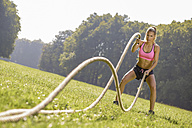 Young woman training with workout ropes on a meadow - MAD000029