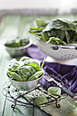 Bowl and colander of fresh spinach leaves on cloth and wood - SBDF001269