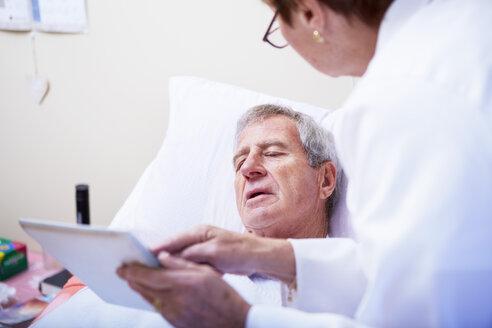 Doctor showing digital tablet to senior man in hospital bed - ZEF000962