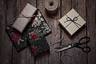 Wrapped christmas gifts, scissors and string on wooden table - CZF000170