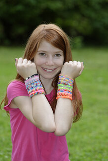 Portrait of happy girl showing self-made looms at her wrists - LBF000955