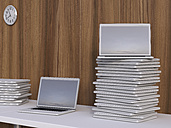Stacks of laptops on a table in front of wooden wall, 3D Rendering - UWF000196