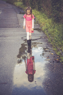 Little girl looking at her mirror image on a puddle - SARF000863