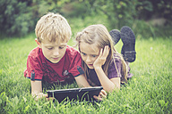 Brother and sister lying on a meadow using digital tablet - SARF000867