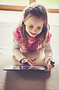 Portrait of little girl sitting on the floor  using digital tablet - SARF000870